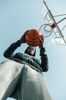 농구 게임. 좋은 아프리카 계 미국인 남자의 손에있는 오렌지 농구 공의 낮은 각도