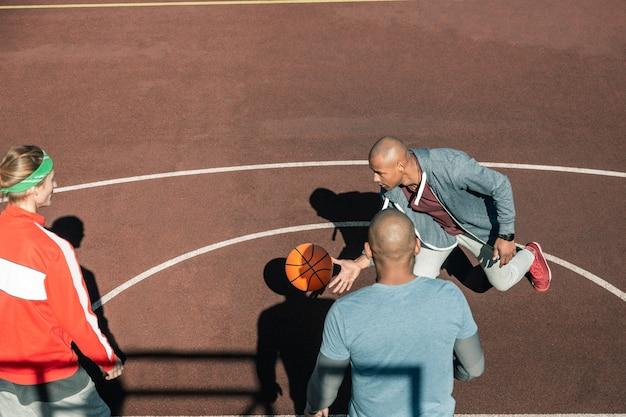 농구 게임. 농구를하는 동안 공을 잡는 즐거운 젊은 남자의 상위 뷰