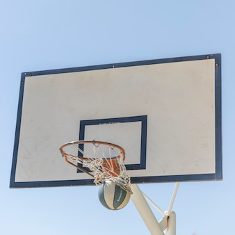 Basketball going through the hoop against clear sky