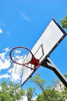 흰 구름과 나무가 있는 밝은 푸른 하늘을 배경으로 농구 후프와 백보드. 아래에서 촬영