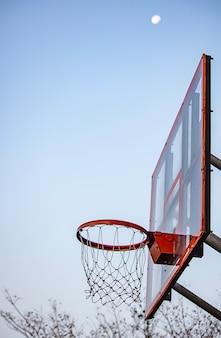 バスケットボールのフープの背景ぼやけて木と空の月。