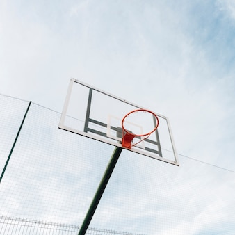 Basketball hoop and net on fence with sky view
