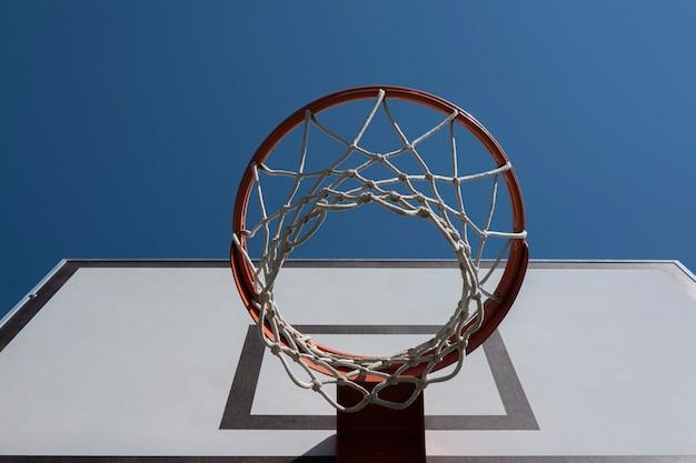 青い空の背景ローアングルビューと屋外バスケットボールコートのバスケットボールフープ