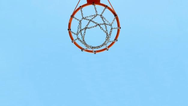 백그라운드에서 푸른 하늘에 대 한 스포츠 코트에 농구 후프. 카피스페이스.