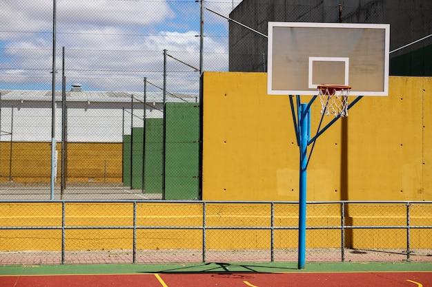 昼間の日光の下で遊び場の柵に囲まれたバスケットボールのフープ