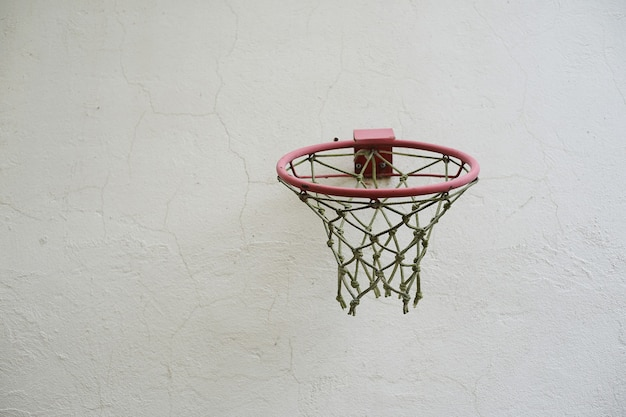 Basketball hoop with net against a white wall outdoor
