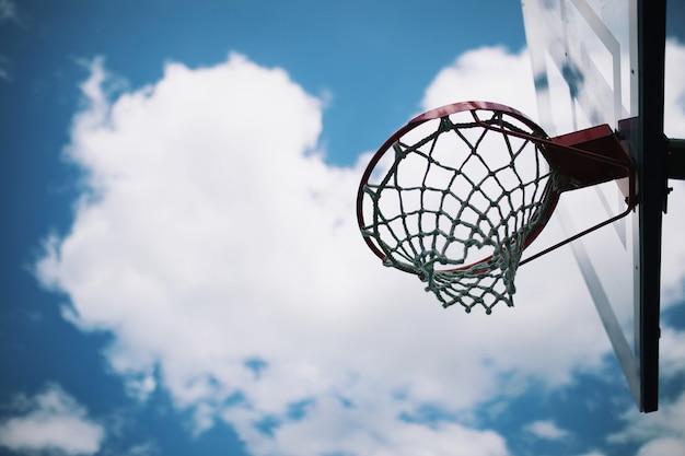 푸른 하늘과 흰 구름 아래 그물이 있는 농구 후프