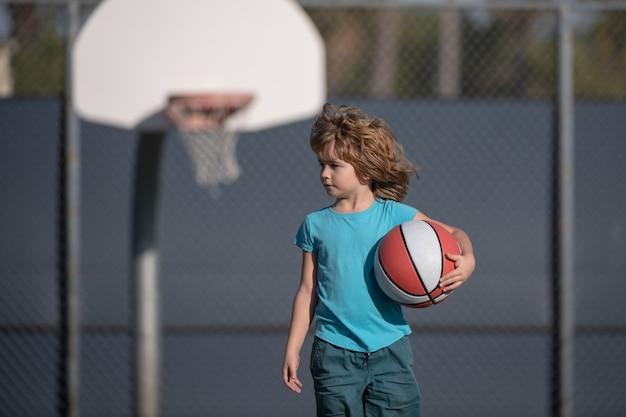バスケットボールキッズトレーニングゲーム。バスケットボールを持つアメリカ人の子供。
