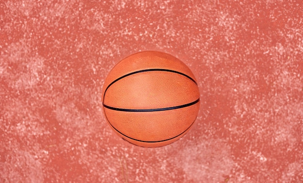 Basketball laying on red ground