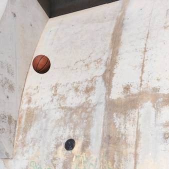 Basketball in mid-air against grunge wall