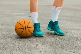 Basketball next to shoes of girl
