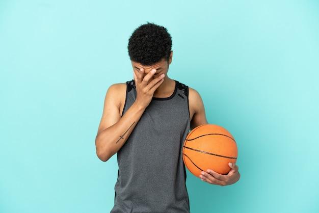 Баскетболист афро-американский мужчина изолирован на синем фоне с усталым и больным выражением лица