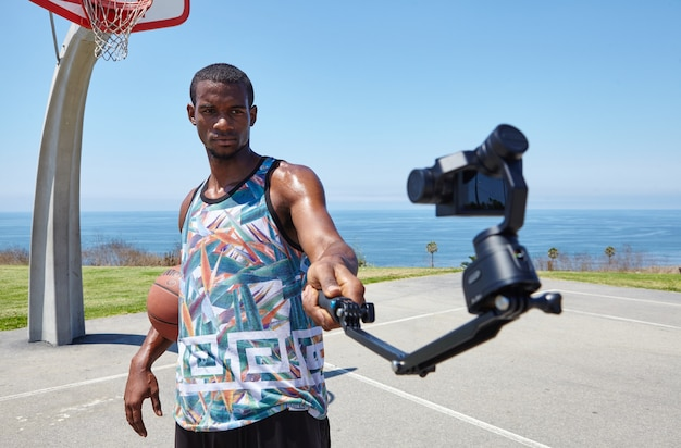 Basketball player by the ocean with selfie camera