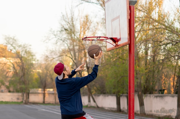 Basketball player doing practice shooting drills outdoor in the city street courts