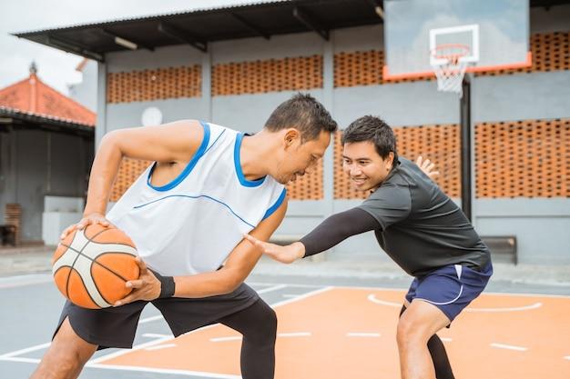 バスケットボール選手が相手選手と顔を合わせてドリブル