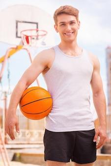 농구 선수. 야외에 서서 웃고 있는 잘생긴 젊은 남자 농구 선수