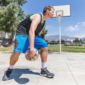 A basketball player holding ball at outdoors court