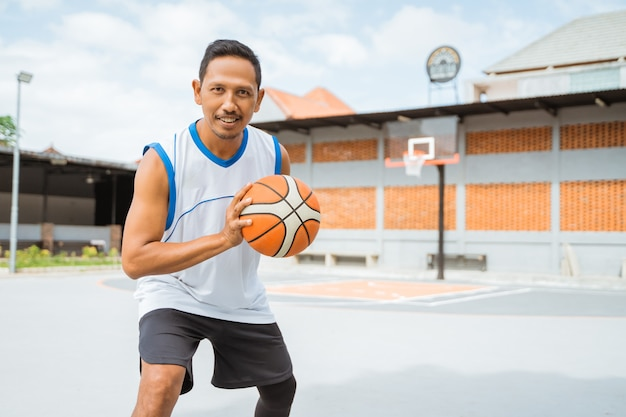 A basketball player holding a basketball with a pose ready to dribble the ball