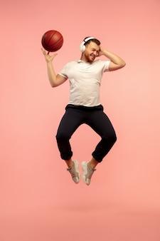 행동에 농구 선수입니다. 핑크 스튜디오 배경에 고립 된 젊은 높이 점프 남자의 전체 길이 초상화. 남성 백인 모델입니다. 카피스페이스. 인간의 감정, 표정, 스포츠 개념.