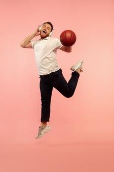 헤드폰에 농구 선수입니다. 핑크 스튜디오 배경에 고립 된 젊은 높이 점프 남자의 전체 길이 초상화. 남성 백인 모델입니다. 카피스페이스. 인간의 감정, 표정, 스포츠 개념.