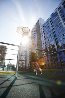 Basketball player jumping in sunlight