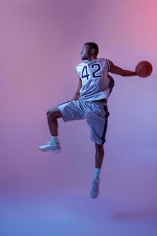 スタジオ、ネオンの背景でボールとジャンプするバスケットボール選手。スポーツゲームをプレイするスポーツウェアのプロの男性バラー
