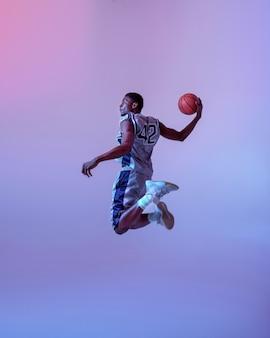 ボールでジャンプするバスケットボール選手。スポーツゲームをするスポーツウェアのプロの男性バラー、背の高いスポーツマン