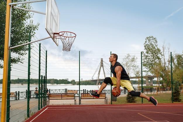 Баскетболист делает бросок в прыжке, на открытом воздухе