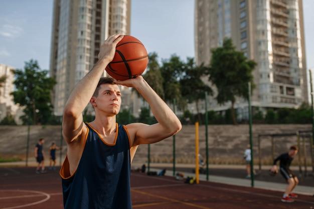 Баскетболист делает бросок на открытой площадке