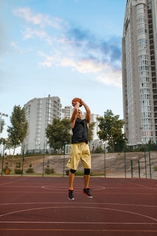 Basketball player makes a throw on outdoor court.