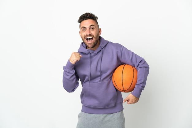 우승자 위치에서 승리를 축하하는 흰색 배경에 고립 된 농구 선수 남자