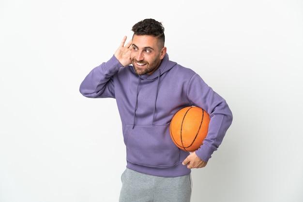 耳に手を置くことによって何かを聞いて白い背景で隔離のバスケットボール選手の男