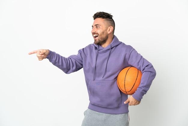 Человек баскетболиста изолирован на белом фоне, указывая пальцем в сторону и представляя продукт