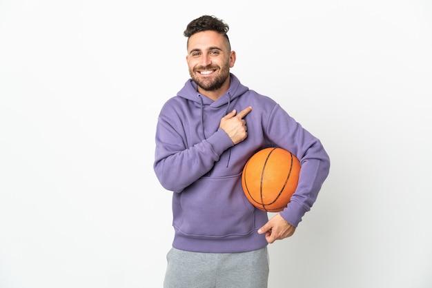 Человек баскетболиста изолирован на белом фоне, указывая в сторону, чтобы представить продукт