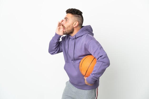 Человек баскетболиста изолирован на белом фоне кричит с широко открытым ртом в сторону