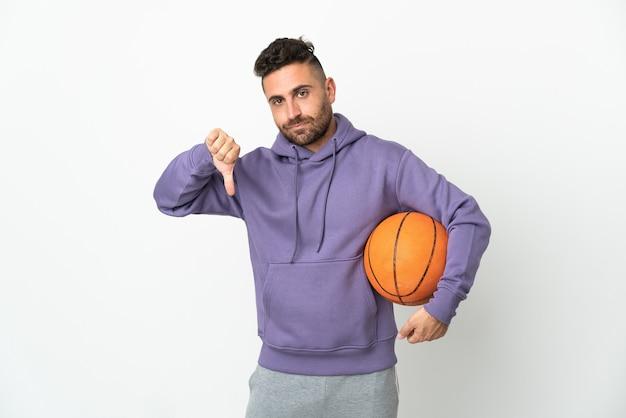 Человек баскетболиста изолирован на белом фоне, показывая большой палец вниз с отрицательным выражением лица