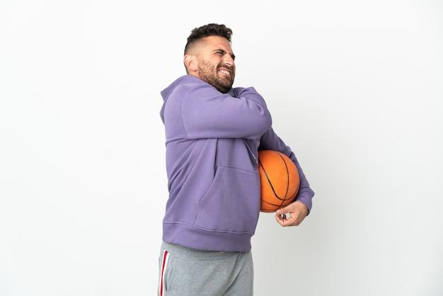 Человек баскетболиста изолирован на белом фоне страдает от боли в плече за то, что приложил усилие