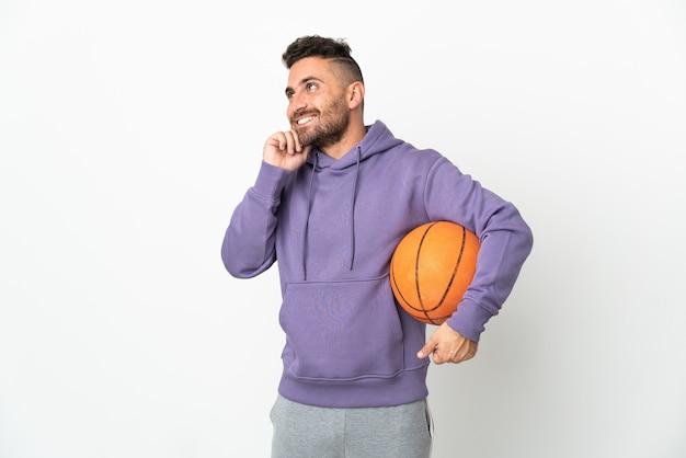 Человек баскетболиста изолирован на белом фоне, думая об идее, глядя вверх