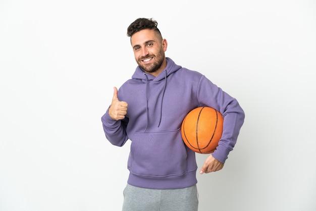 좋은 일이 일어났기 때문에 엄지 손가락으로 흰색 배경에 고립 된 농구 선수 남자