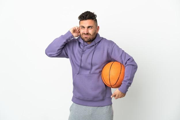 欲求不満と耳を覆っている白い壁に孤立したバスケットボール選手の男