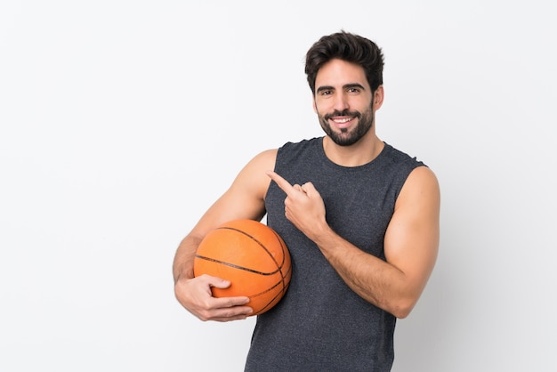 Basketball player man with beard over isolated white wall pointing to the side to present a product