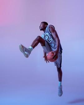 スタジオ、ネオンの背景にボールを持って移動するバスケットボール選手。スポーツゲームをするスポーツウェアのプロの男性バラー、背の高いスポーツマン