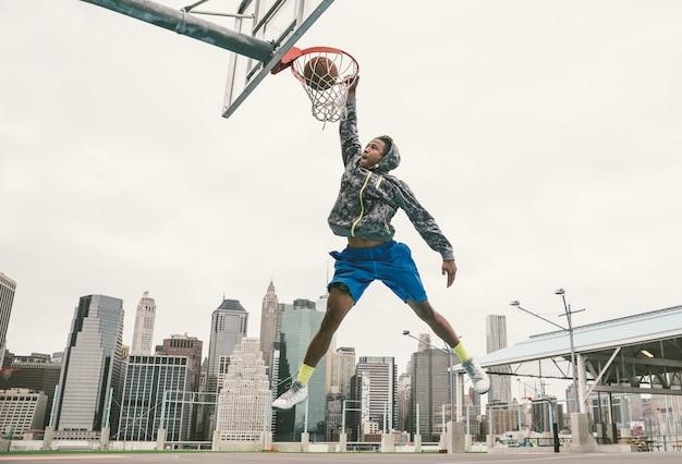 Basketball player performing slum dunk on a street court.