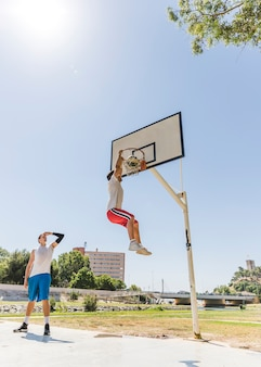 Basketball player performing slum dunk on a street court