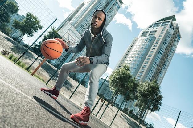 농구 선수. 농구 코트에 서있는 동안 공을 가지고 노는 즐거운 젊은 남자
