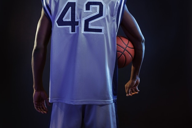 Basketball player poses with ball, back view. professional male baller in sportswear playing sport game, tall sportsman