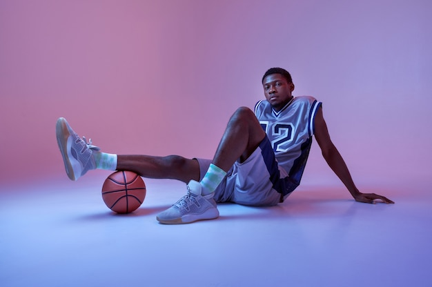Basketball player poses with ball. professional male baller in sportswear playing sport game, tall sportsman