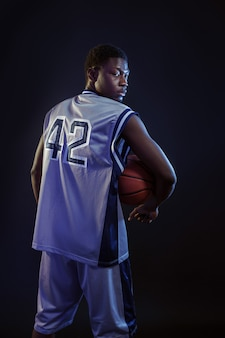 Basketball player poses with ball in studio, back view, black background. professional male baller in sportswear playing sport game, tall sportsman