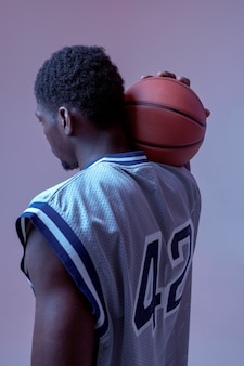 Basketball player poses with ball in studio, back view, neon background. professional male baller in sportswear playing sport game, tall sportsman