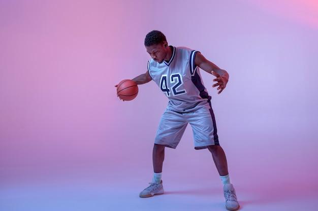 ボールで練習しているバスケットボール選手。スポーツゲームをするスポーツウェアのプロの男性バラー、背の高いスポーツマン